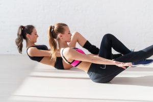 Two sporty women doing exercise abdominal crunches