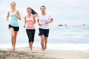 Running friends on beach jogging group training.