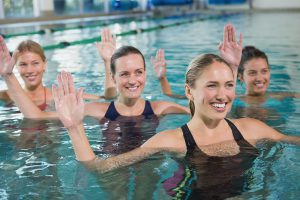 Smiling female fitness class doing aqua aerobics in swimming poo